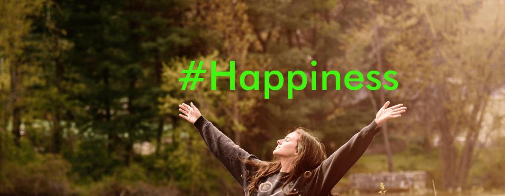 felicidad mujer feliz en el bosque sostiene letrero happines con brazos abiertos sobre la cabeza
